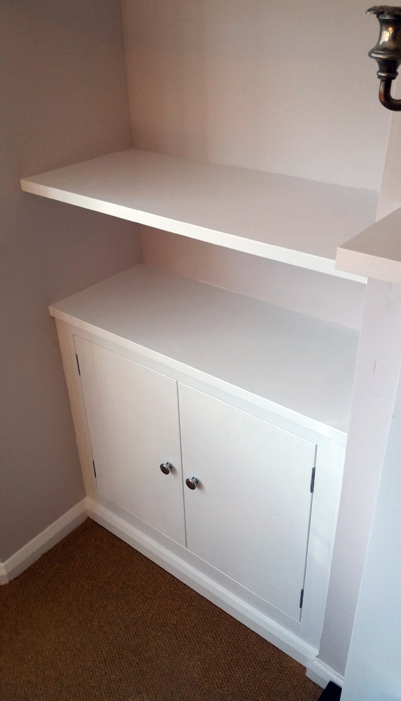 Bespoke fitted cupboard within an alcove.